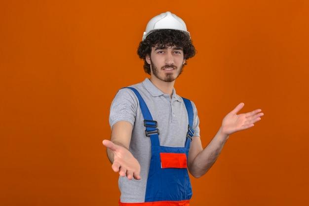 Junger bärtiger hübscher baumeister, der bauuniform und sicherheitshelm trägt, der die kamera betrachtet, die mit offenen armen für umarmung über isolierter orange wand lächelt