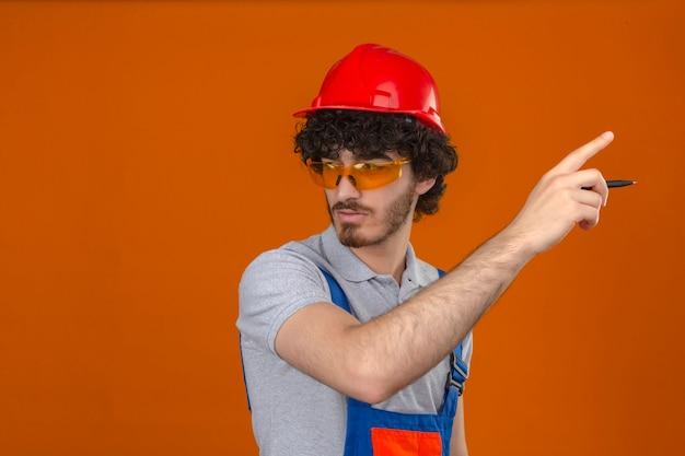 Junger bärtiger hübscher baumeister, der bauuniformbrille und sicherheitshelm trägt, der beiseite hält, stift in der hand hält und mit ernstem gesicht über isolierte orange wand zeigt