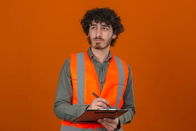 Junger bärtiger hübscher ingenieur, der bauweste hält, die klemmbrett hält, das etwas schreibt, das nachdenklichen ausdruck auf gesicht über isolierter orange wand beiseite schaut