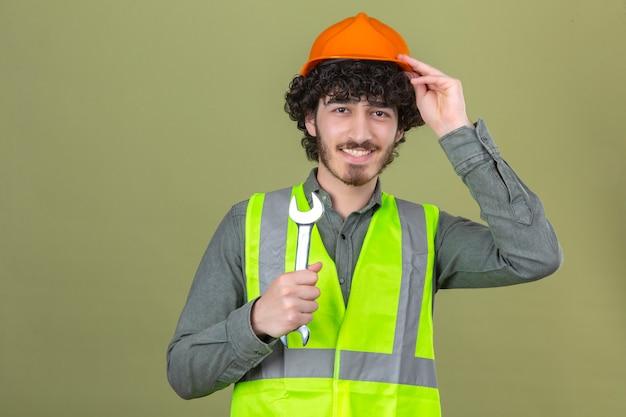 Junger bärtiger hübscher ingenieur, der schraubenschlüssel berührt helm mit hand mit lächeln auf gesicht über isolierter grüner wand hält