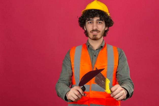 Junger bärtiger hübscher ingenieur, der sicherheitshelm und weste trägt, die kittmesser mit lächeln auf gesicht über isolierter rosa wand halten