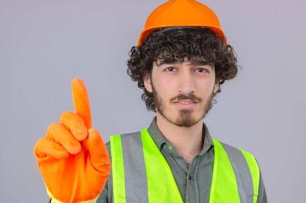 Junger bärtiger hübscher ingenieur, der sicherheitshelm und weste trägt, die zeichen nummer eins mit lächeln über isolierter weißer wand zeigt
