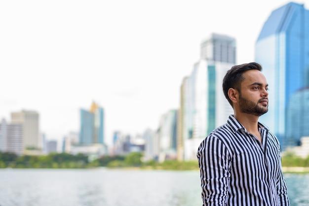Junger bärtiger indischer geschäftsmann, der am park entspannt