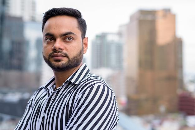 Junger bärtiger indischer geschäftsmann gegen ansicht der stadt