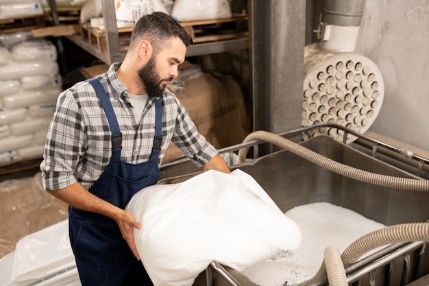 Junger bärtiger ingenieur der kunststoffpolymerproduktionsfabrik, der durch großen behälter steht, während weiße pellets verstreut werden