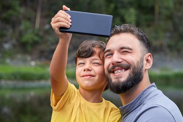 Junger bärtiger kaukasischer mann und sein sohn lächeln, während auf kamera auf handy schauen