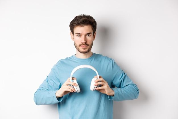 Junger bärtiger kerl in blauem sweatshirt setzt drahtlose kopfhörer auf, hört musik und steht auf weißem hintergrund.