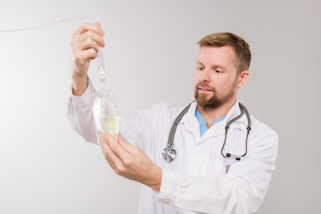 Junger bärtiger kliniker mit stethoskop, der transparenten tropfensack mit flüssiger medizin hält, während vor der kamera isoliert steht