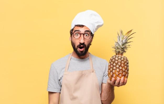 Junger bärtiger koch mann erschrocken ausdruck mit einer ananas