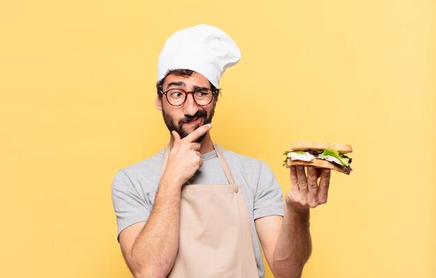 Junger bärtiger kochmann, der zweifelt oder einen unsicheren ausdruck hat und ein sandwich hält?