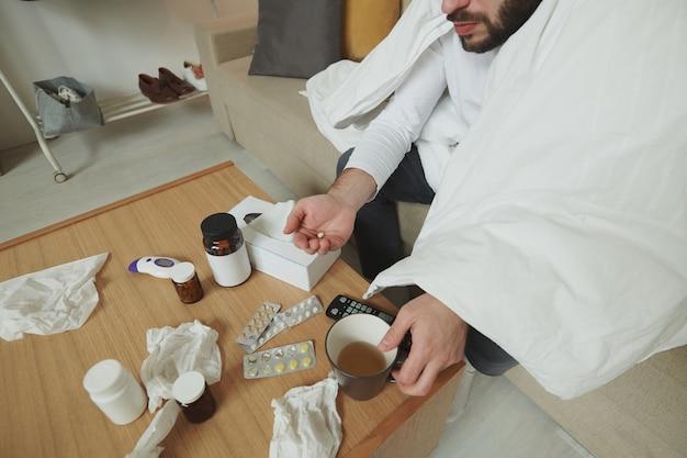 Junger bärtiger kranker mann, der auf couch durch kleinen holztisch sitzt und tablette nimmt, während zu hause für selbstisolation bleibt