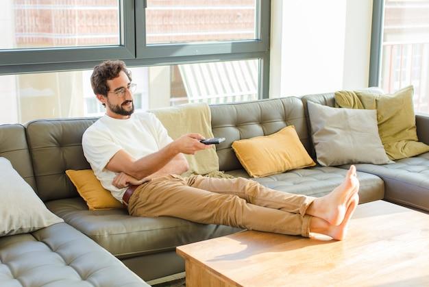 Junger bärtiger kühler mann, der auf einer couch zu hause sitzt