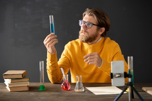 Junger bärtiger lehrer der chemie, der röhre mit rosa flüssiger substanz während der online-lektion vor der smartphone-kamera betrachtet