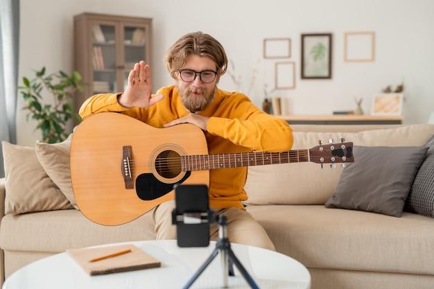 Junger bärtiger lehrer, der sein online-publikum zu beginn der lektion des gitarrenspiels beim betrachten in der smartphone-kamera begrüßt
