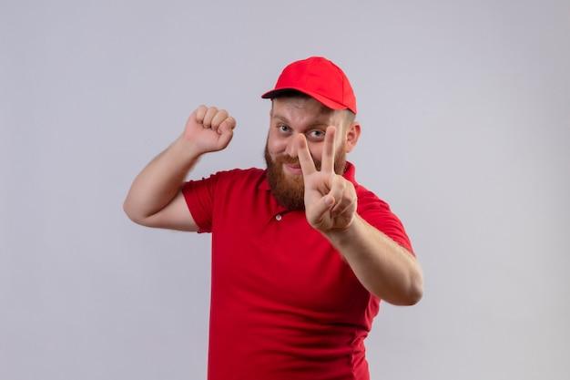 Junger bärtiger lieferbote in der roten uniform und in der geballten faust der kappe, die siegeszeichen lächelnd zeigt