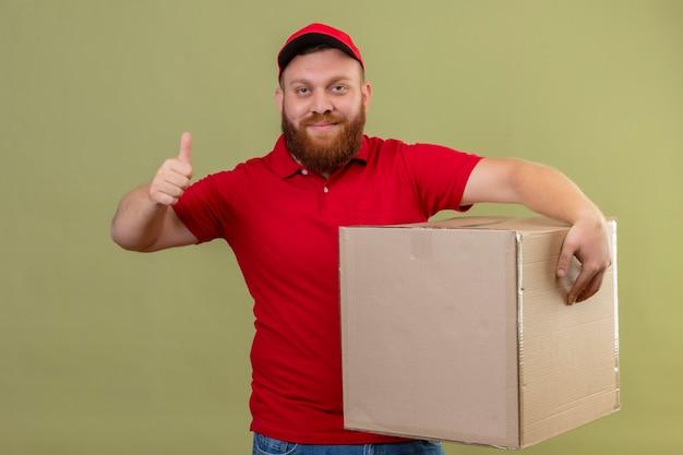 Junger bärtiger lieferbote in der roten uniform und in der kappe, die den karton hält, der kamera mit dem selbstbewussten lächeln betrachtet, das daumen oben zeigt