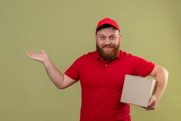 Junger bärtiger lieferbote in der roten uniform und in der kappe, die den pappkarton hält, der kamera mit dem selbstbewussten lächeln betrachtet, das mit arm seiner hand präsentiert