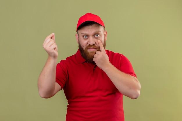 Junger bärtiger lieferbote in der roten uniform und in der kappe, die kamera betrachtet, die mit finger zu seinem auge zeigt, reibt finger, macht geldgeste und wartet auf zahlung