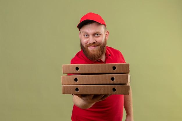 Junger bärtiger lieferbote in der roten uniform und in der kappe, die stapel von pizzaschachteln hält, die freundlich lächeln
