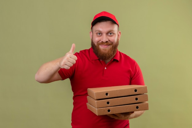 Junger bärtiger lieferbote in der roten uniform und in der kappe, die stapel von pizzaschachteln hält, die kamera lächelnd zeigt daumen hoch