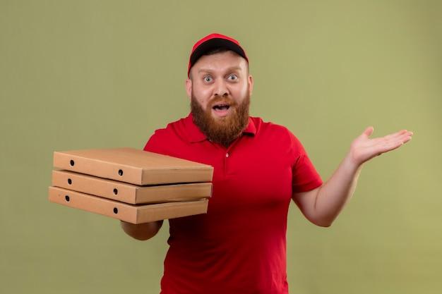 Junger bärtiger lieferbote in der roten uniform und in der kappe, die stapel von pizzaschachteln halten, die besorgt und verwirrt mit erhobenen armen schauen