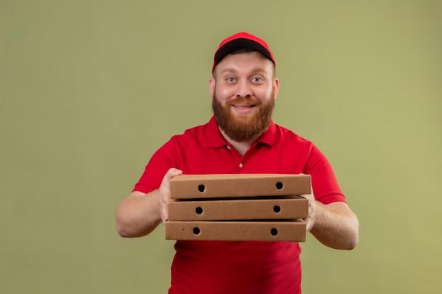 Junger bärtiger lieferbote in der roten uniform und in der kappe, die stapel von pizzaschachteln hockt, die kamera freundlich lächelnd betrachten