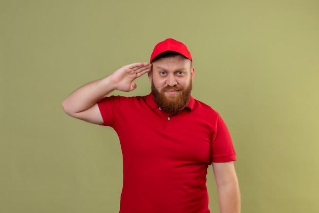 Junger bärtiger lieferbote in der roten uniform und in der mütze, die zuversichtlich salutiert