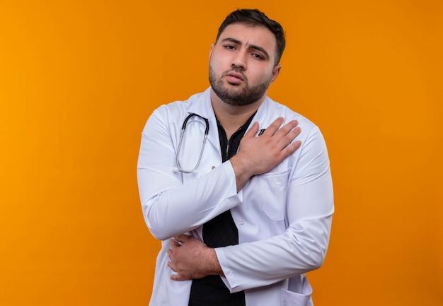Junger bärtiger männlicher arzt, der weißen kittel mit berührendem schultergefühlschmerz trägt