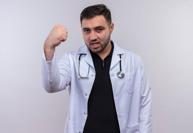 Junger bärtiger männlicher arzt, der weißen kittel mit geballter faust des stethoskops mit wütendem gesicht trägt
