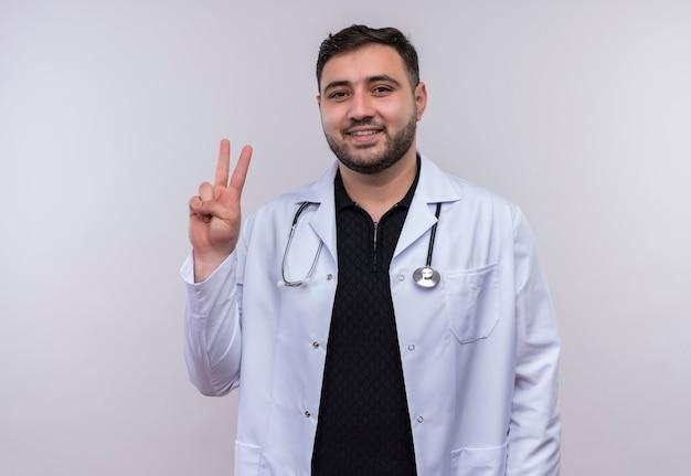 Junger bärtiger männlicher arzt, der weißen kittel mit lächelndem stethoskop trägt, das nummer zwei oder siegeszeichen zeigt