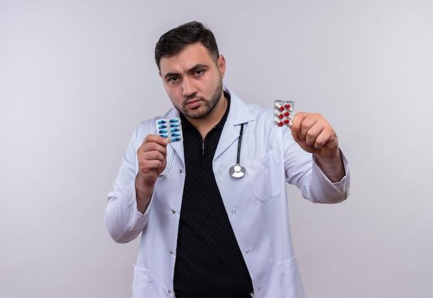 Junger bärtiger männlicher arzt, der weißen kittel mit stethoskop hält, das blasen mit pillen hält, die kamera mit ernstem gesicht zeigen