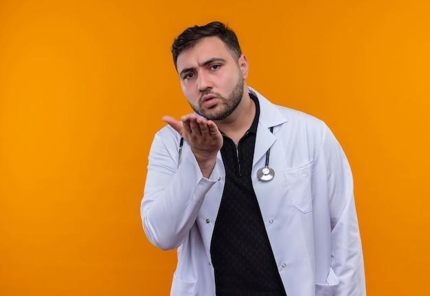 Junger bärtiger männlicher arzt, der weißen kittel mit stethoskop hebt, das arm erhöht, der mit der hand als frage gestikuliert