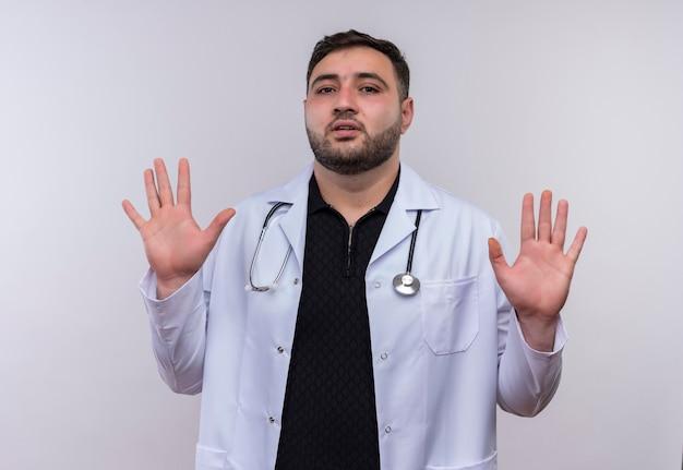 Junger bärtiger männlicher arzt, der weißen kittel mit stethoskop trägt, das arme in der übergabe mit angstausdruck anhebt