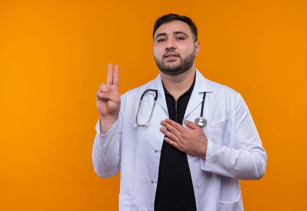 Junger bärtiger männlicher arzt, der weißen kittel mit stethoskop trägt, das hand hebt und eide tut, die zuversichtlich schauen