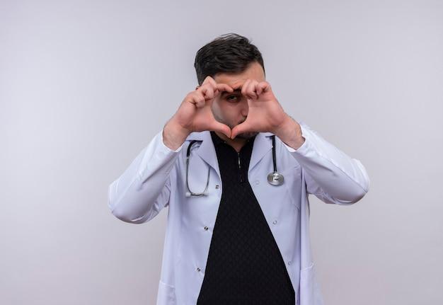 Junger bärtiger männlicher arzt, der weißen kittel mit stethoskop trägt, das herzgeste mit den fingern macht, die durch finger schauen