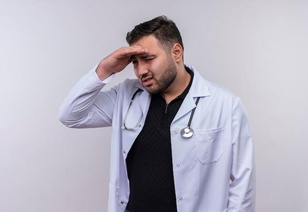 Junger bärtiger männlicher arzt, der weißen kittel mit stethoskop trägt, das weit weg mit hand über kopf schaut, um etwas oder jemanden zu schauen