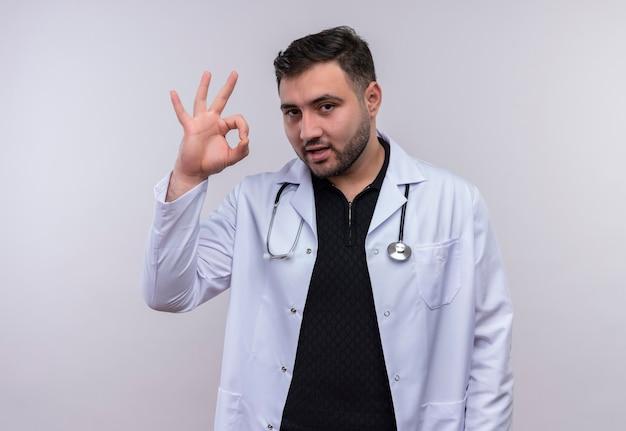 Junger bärtiger männlicher arzt, der weißen mantel mit lächelndem stethoskop trägt, das ok zeichen über weißem hintergrund tut