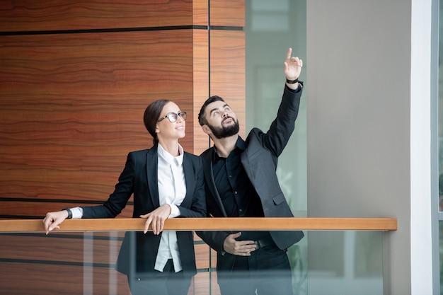 Junger bärtiger manager in der jacke, der auf balkon des bürozentrums steht und nach oben zeigt, während er kollege über expansion des unternehmens erzählt