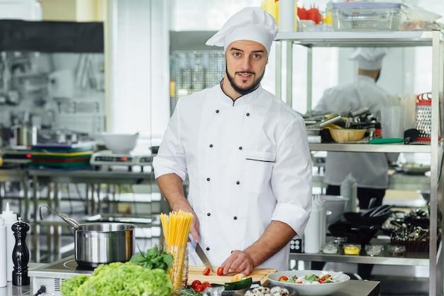 Junger bärtiger mann an seinem arbeitsplatz, der gemüse kocht