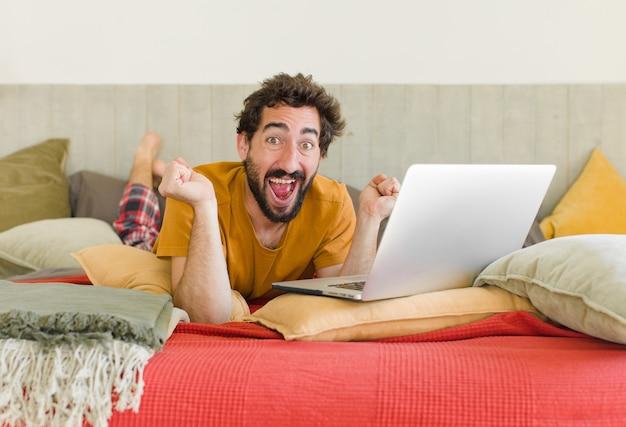 Junger bärtiger mann auf einem bett mit einem laptop