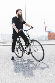Junger bärtiger mann, der auf dem fahrrad weg schaut sitzt