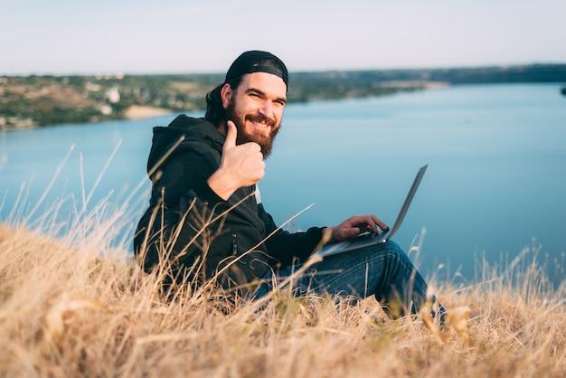 Junger bärtiger mann, der auf einem feld mit seinem lächelnden computer sitzt und einen daumen in der nähe eines flusses hochhält