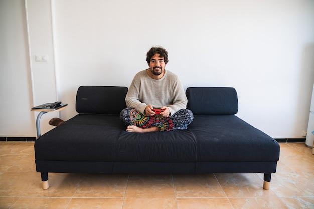 Junger bärtiger mann, der auf einer sofakonsole sitzt