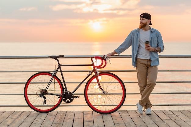 Junger bärtiger mann, der auf fahrrad am sonnenuntergangmeer reist