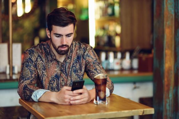 Junger bärtiger mann, der die zufällige kleidung betrachtet seinen smartphone in einer modernen kneipe trägt