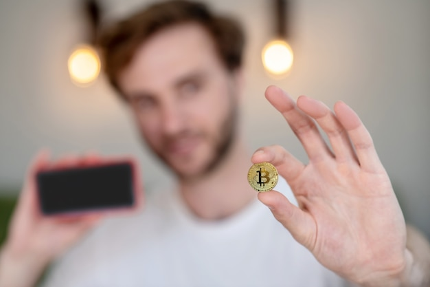 Junger bärtiger mann, der ein bitcoin in der hand hält