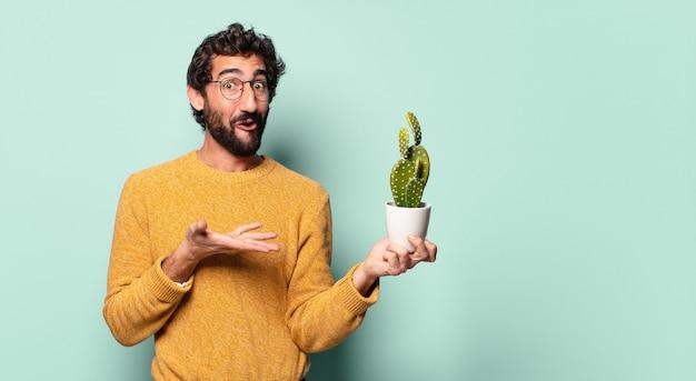 Junger bärtiger mann, der eine kaktus-zimmerpflanze hält