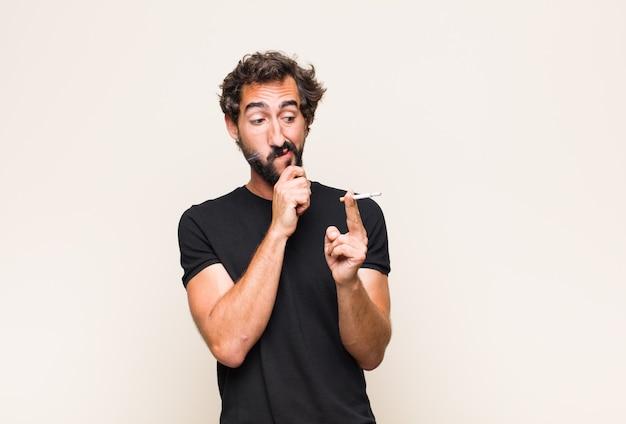 Junger bärtiger mann, der eine zigarette raucht