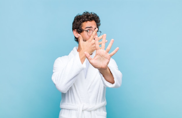 Junger bärtiger mann, der einen bademantel trägt, der gesicht mit hand bedeckt und andere hand vorne legt, um vorne anzuhalten, fotos oder bilder ablehnend