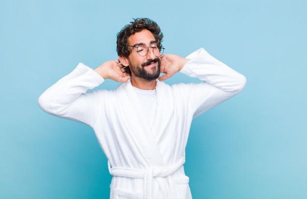 Junger bärtiger mann, der einen bademantel trägt, der lächelt und sich entspannt, zufrieden und sorglos fühlt, positiv lacht und kühlt Premium Fotos